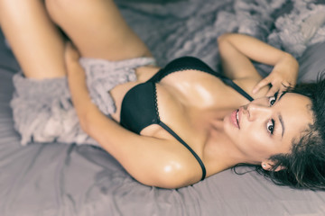 Beautiful exotic young woman lying in bed