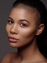 Fototapete - Fashionable portrait of an extraordinary beautiful african american model with perfect smooth glowing skin, full lips and shaved haircut, studio shoot, dark background