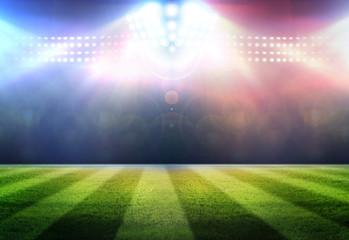 Stadium football game lights are shinning on a green grass field