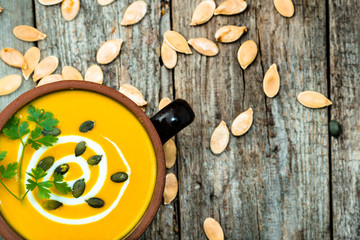 Pumpkin soup with cream in a bowl on wooden table, top view