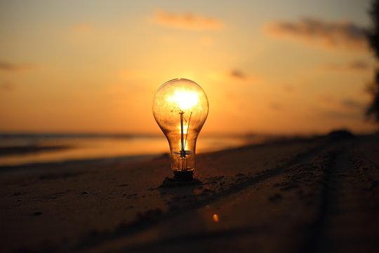 electric light bulb and sun at beach sunset sky