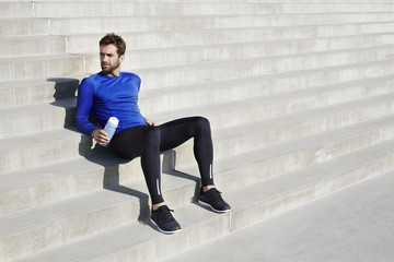 Athlete taking a break on steps, looking away