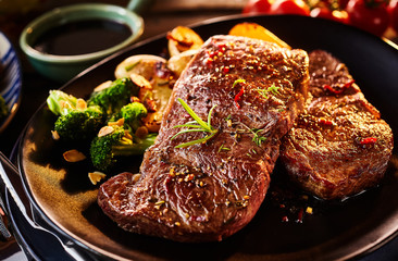 Two pieces of cooked sirloin steak with veggies