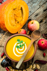 Pumpkin soup with cream and parsley, healthy food cooking concep