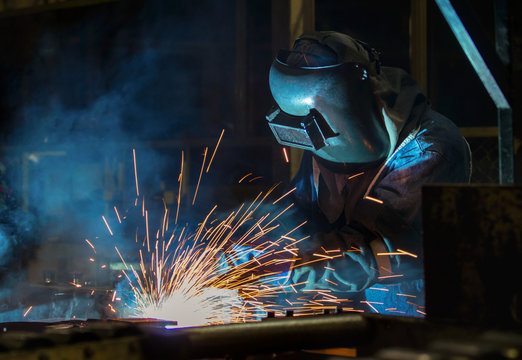 Worker with protective mask welding automotive part in factory