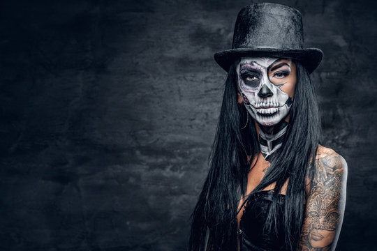 A woman with skull make up in top hat on Halloween.