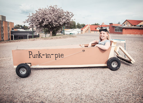 Young girl in a soap-box car named 'Punk-in-pie'