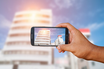 Man hand holding smart phone focused on city landscape