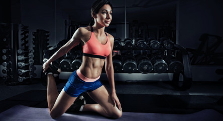 Sports background. Stretching. Athletic woman working in fitness gym