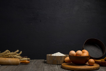 Wall Mural - Flour and eggs on a wooden table on dark background
