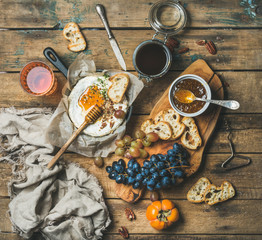 Cheese, fruit and wine set. Camembert in small pan, honey, fig jam, persimmon, grapes, pecan nuts, grilled baguette slices and glass of rose wine over rustic wooden background, top view