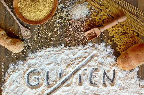 Wall mural Gluten free cereals corn, rice, buckwheat, quinoa, millet, pasta and flour with scratched text gluten on brown wooden background