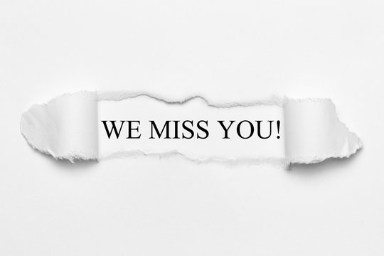 We miss you! on white torn paper