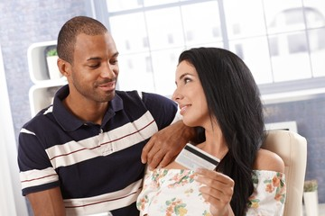 Young couple with credit card smiling