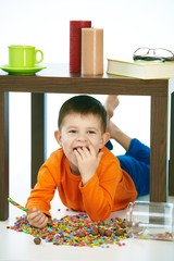 Naughty little kid eating sweets under table