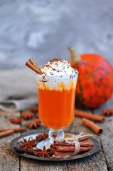 Pumpkin smoothie with cinnamon and whipped cream on a wooden background.