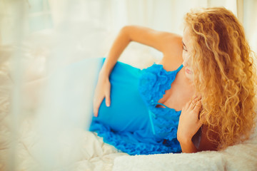 charming blonde lying on a large white sofa