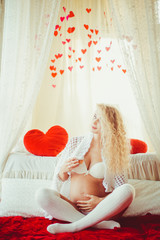 pregnant woman posing for the camera in a beautiful bedroom