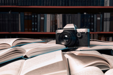 Old photo camera  is on many  open books piled up with many book