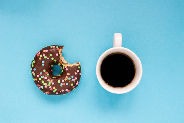 Chocolate donuts with cup of coffee on the blue background.