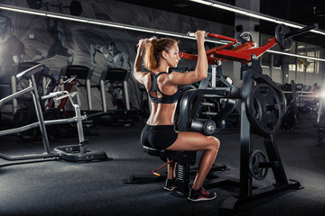 Muscular fitness woman doing exercises in the gym.