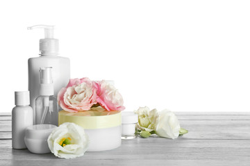 Different cosmetic bottles and eustoma flowers on white background