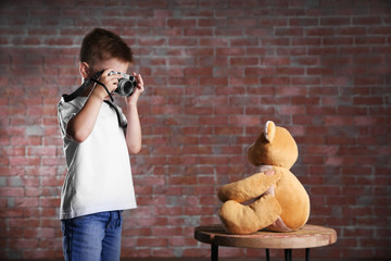 Little boy taking photo of toy bear on brick wall background