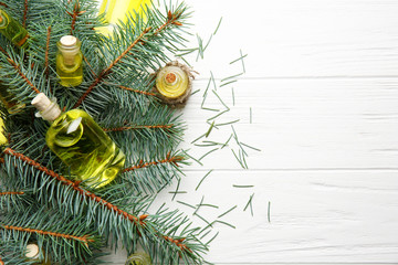 Bottles of coniferous essential oil and branches on wooden background