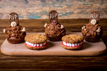 Dentures for Halloween made of cookies and marshmallow and Halloween cupcakes with tombstone