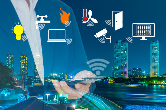 Smart Building and Internet of Things concept. Smart building management icons on Double Exposure image of Businessman use smart phone and City Building at night.