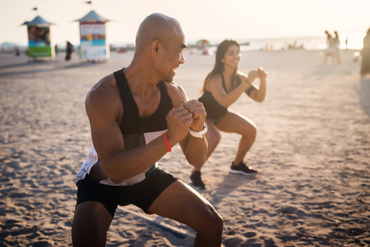 Man and woman at the beach, working out.