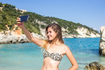 lifestyle, leisure, summer, technology and people concept - smiling young woman or teenage girl in sun hat taking selfie with smartphone on beach