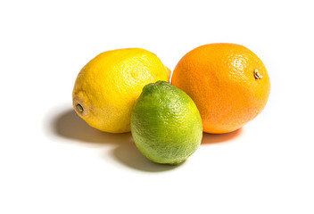 Whole citruses of different colors on white. Lemon, orange and lime