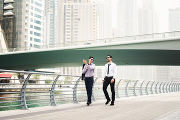 Two businessmen having a conversation while walking though Dubai Marina.