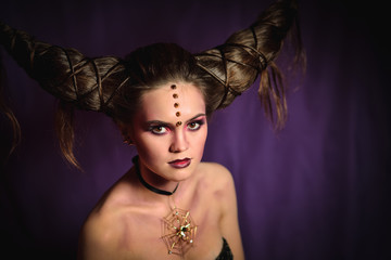 Woman in Halloween makeup with hairstyle in form of horns, Devil Queen