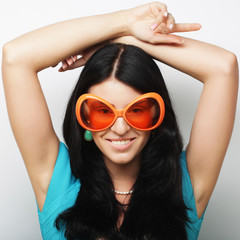 Playful young woman with big party glasses and crown.