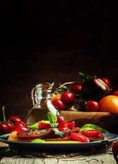 Salad of colorful tomatoes on plate. Vintage wooden background,