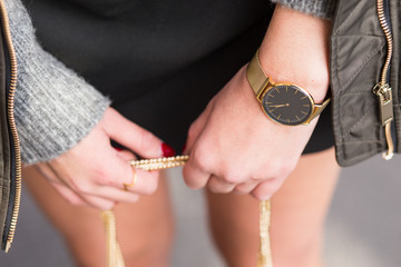 close up fashion details, young business woman holding her bag. wearing golden jewelry, and watch. graded in warm colors.