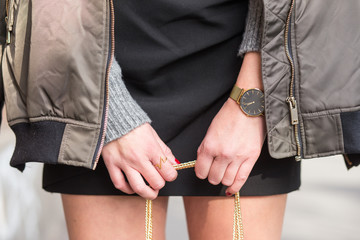 close up fashion details. young stylish woman holding her bag with a golden chain. wearing golden jewelry, grey warm sweater and a golden watch. graded in warm colors.