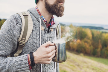 Young man traveler holding cup with hot drink.Travel and active lifestyle concept