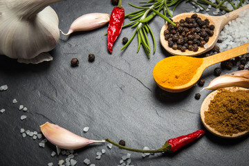 spices and herbs over black stone background, top view with copy space