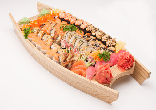 assortment of sushi in wooden boat plate on a white background