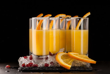 a few glasses of orange drink and ice on a black stone on a dark background