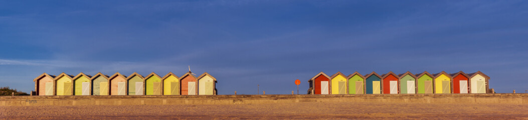 Colourful beach huts at South Beach, Blyth, Northumberland, England, UK. In early morning sunlight. Panoramic view