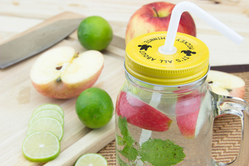 mojito in mason`s jar with ice cubes, decorated by mint leaf, lime fruits, masher, cutting board, knife, bottle,apple, on turquoise colored wooden table