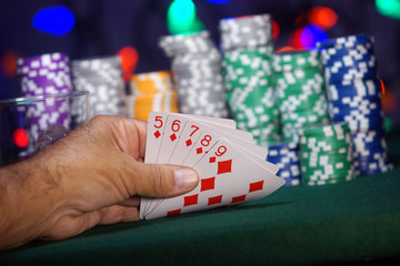 Hand holding a Straight Flush in the card game of poker