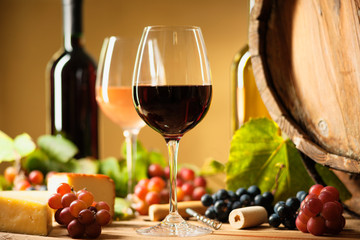 Wine bottle, glasses, cheese, grapes and barrel