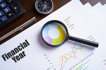 """Financial Year"" text on paper sheet with magnifying glass on chart, dice, spectacles, pen, laptop and blue and yellow push pin on wooden table - business, banking, finance and investment concept"
