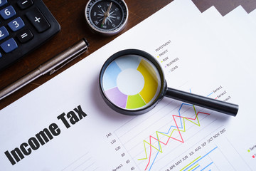 """Income Tax"" text on paper sheet with magnifying glass on chart, dice, spectacles, pen, laptop and blue and yellow push pin on wooden table - business, banking, finance and investment concept"