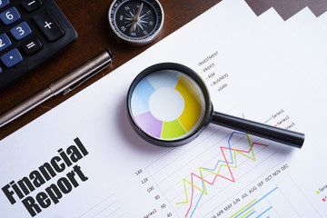 "Magnifying glass on colourful pie chart with ""Financial report"" text on paper, dice, spectacles, pen, laptop calculator on wooden table - business, banking, finance and investment concept"